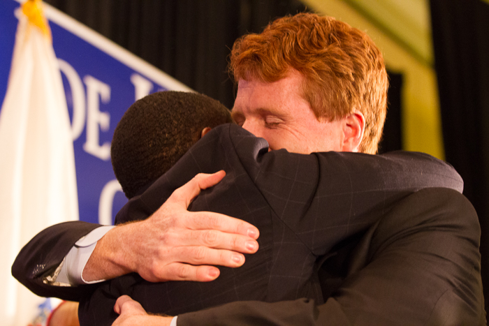 Newly elected Representative Joe Kennedy of Massachusetts embraces Mayor Setti Warren of Newton MA, as he enters the stage to give his victory speech at the Newton Marriot on Tuesday night (Photo by Alexa Gonzalez Wagner/BU News Service)
