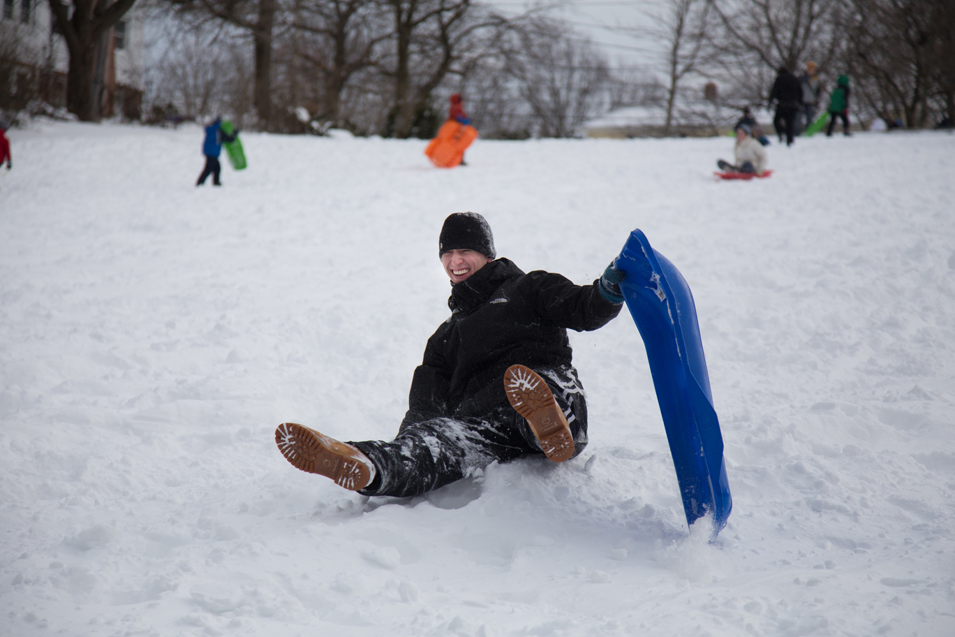 Image: Jonah Lundberg of Allston, Mass., topples off of his sled on Corey Hill in Brighton on Saturday afternoon. (Photo by Alexa Gonzalez Wagner/BU News Service)