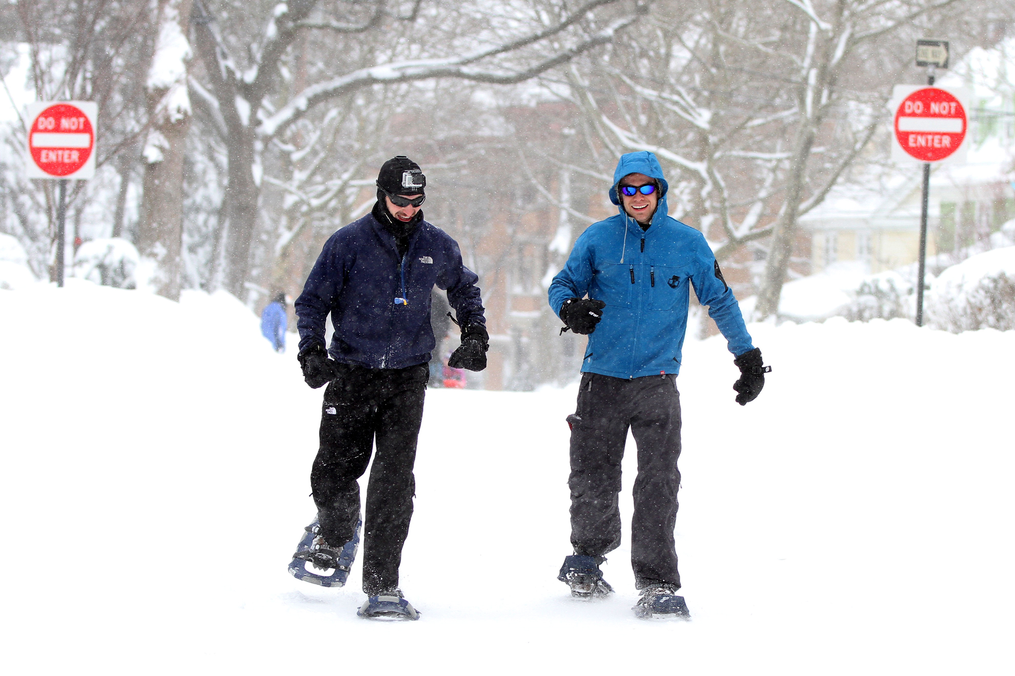 Image: Brookline residents Thomas Battey (left) and Vincent Valant walk with snowshoes down Fuller Street on Saturday after a winter storm passed through the Northeast, leaving over 20 inches of snow in the city of Boston. (Photo by Billie Weiss/BU News Service)