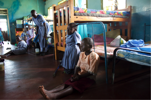 Joyland primary school pupils sit in the girls'  dormitory.