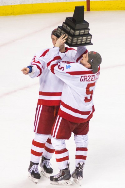 Boston, Mass, U.S. March. 21, 2015. Boston University's Jack Eichel, left, and Matt Grzelcyk, right, celebrate with the Lamoriello Trophy after winning the Men's Hockey East championship game against the University of Massachusetts Lowell at TD Garden. BU won 5-3. (Photo by: Jun Tsuboike/BU News Service)