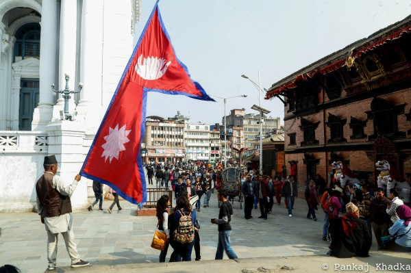 Kathmandu, Nepal. A man waves a Nepali flag on a busy corner in Basantapur, the Kathmandu Durbar Square. Usually bustling with tourists and locals, the historic site was severely damaged and the white palace behind the man holding the flag, a part of which appears on the left corner, has crumbled to the ground following the catastrophic earthquake in Kathmandu.