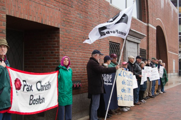 Boston. April 21, 2015. Protestors opposing the death penalty stand outside the John Joseph Moakley United States Courthouse with sings and banners on the opening day of the sentencing trial of Dzokhar Tsarnaev, who was found guilty of all 30 charges for his role in the 2013 Boston Marathon which resulted in death of four, including a police officer, and injured many others. (Photo by: Haiyun Jiang/BU News Service)