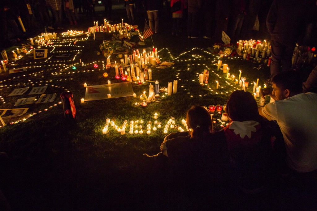 April 26, 2015. Somerville's Sandip Bhattari, Puja Thapa, and Durga Shah look over candles lit during a vigil on Copley Square for the victims of the earthquake in Nepal . (Jun Tsuboike/BU News Service)