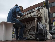 """IMAGE: October 4, 2013 CAMBRIDGE -- Fabio Tedde plays a public piano in Brattle Square on Friday afternoon. There are 75 pianos across Boston for Luke Jerram's """"Play Me, I'm Yours"""" exhibit, which has put temporary street pianos in over thirty cities in the past five years. Tedde, an Italian street performer, follows the piano exhibits and tries to play them all -- this his 38th in Boston and his 434th worldwide. (Photo by Poncie Rutsch.)"""
