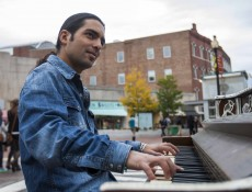 """IMAGE: October 4, 2013 CAMBRIDGE -- Fabio Tedde plays a public piano in Brattle Square on Friday afternoon. There are 75 pianos spread across Boston for Luke Jerram's """"Play Me, I'm Yours"""" exhibit. Tedde, an Italian street performer, follows the piano exhibits and tries to play them all. """"99 percent of the time I improvise,"""" Tedde says, explaining that he used to read music but has long forgotten how. (Photo by Poncie Rutsch.)"""