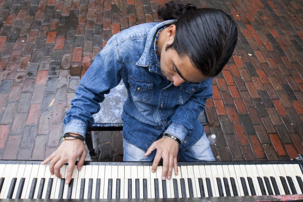 """IMAGE: October 4, 2013 CAMBRIDGE -- Fabio Tedde plays a public piano in Harvard Square on Friday afternoon. There are 75 pianos around Boston for Luke Jerram's """"Play Me, I'm Yours"""" exhibit, which has put temporary street pianos in over thirty cities in the past five years. Tedde, an Italian street performer, follows the piano exhibits and tries to play them all -- this his 37th in Boston and his 433rd worldwide. (Photo by Poncie Rutsch.)"""