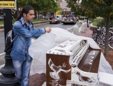 """IMAGE: October 4, 2013 CAMBRIDGE -- Fabio Tedde covers a public piano to protect it from the rain in Brattle Square on Friday afternoon. There are 75 pianos across Boston for Luke Jerram's """"Play Me, I'm Yours"""" exhibit, which has put temporary street pianos in over thirty cities in the past five years. Tedde, an Italian street performer, follows the piano exhibits and tries to play them all. (Photo by Poncie Rutsch.)"""