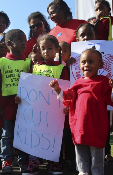 IMAGE: Children stand in front of the Capitol on Oct. 2, 2013 during a rally urging the government to halt spending cuts to Head Start. (Photo: Taylor Hartz, BU News Service)